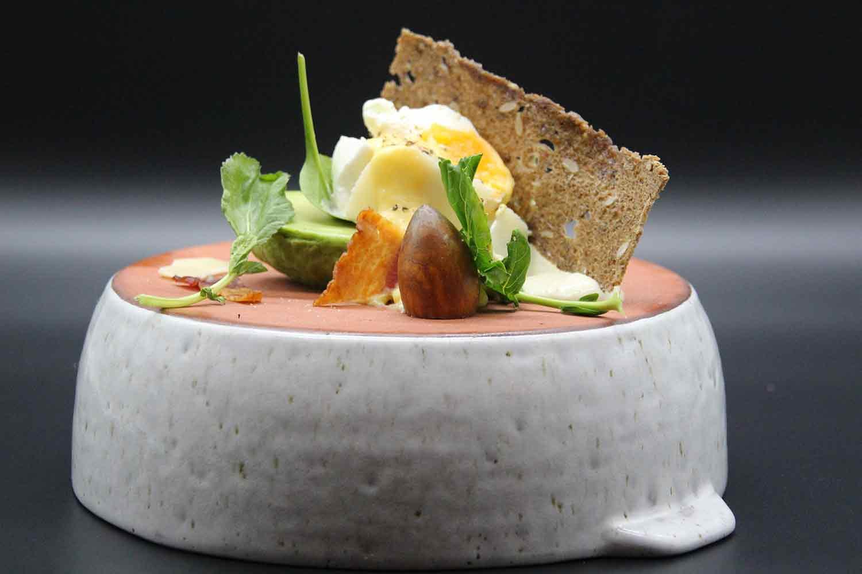 Avocado mit pochiertem Ei, Radieschengrün und Brotcracker